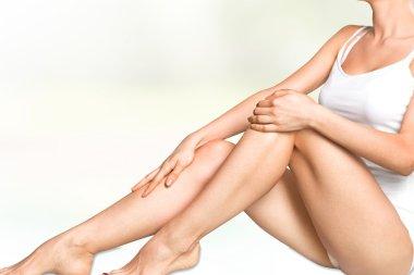 Young woman massaging legs