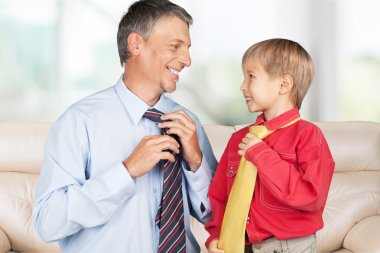 happy boy and his father tying neckties