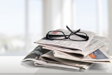Newspapers with reading glasses.