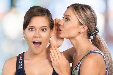 Woman revealing secret to friend