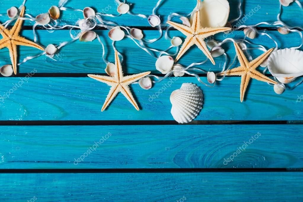 Sea. Delicate nautical border with fishing net, sea shells and starfish on a background of colourful turquoise blue painted wooden boards with copyspace for your text