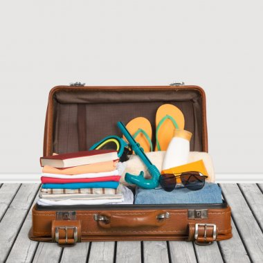 Travel. Packed vintage suitcase full of vacation items