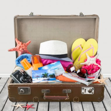 Summer. Retro suitcase with full of clothes,books and passport on blue background