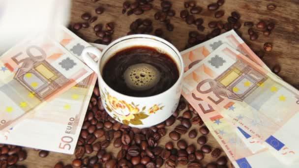 Szemes kávé, kávéscsésze és egy fából készült asztal Euro