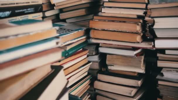 Stoh knih rozházených po podlaze v knihovně