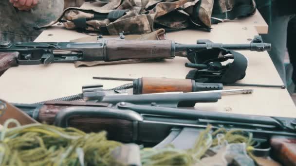 Fegyverek, a automata gépek, gránátok, lőszer, golyó van az asztalon, és a katonai