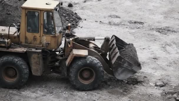 Eine alte Planierraupe auf Gummirädern arbeitet auf der Baustelle.