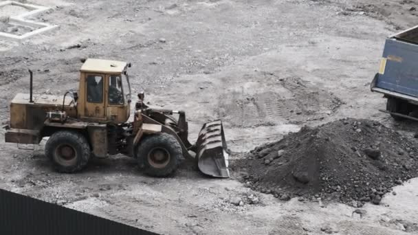 An Old Bulldozer on Rubber Wheels Works on Construction Site.