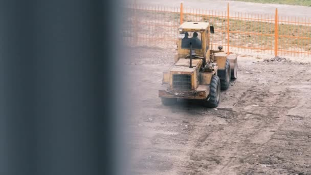 Starý buldozer na gumových kolech pracuje na staveništi.