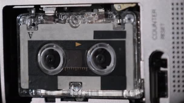 Die Mikrokassette dreht sich in einem tragbaren Handrecorder, Band-Retro-Player