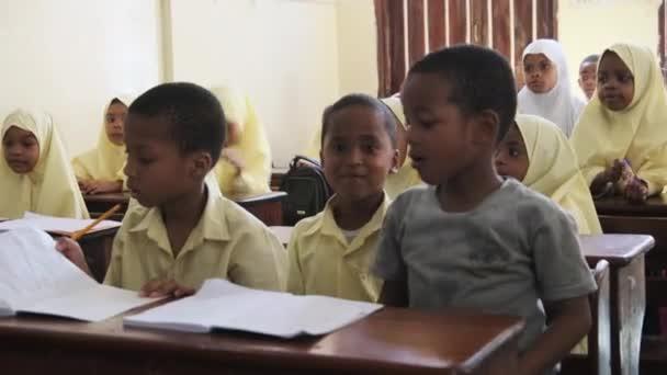 Kinder in einer afrikanischen Grundschule sitzen an Schreibtischen in einem Klassenzimmer, Sansibar