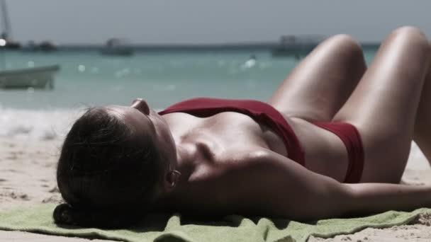 Fiatal nő Sunbathes egy Paradise Sandy Beach fekvő piros fürdőruha közelében Ocean