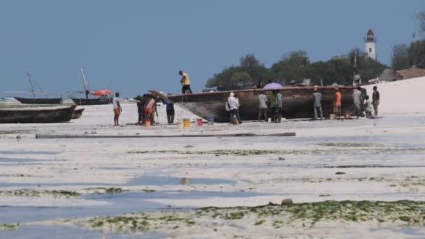 Spousta místních afrických rybářů v blízkosti dřevěné rybářské lodi Dhow na písečném pobřeží