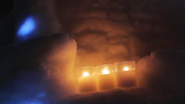 Kerzen werden angezündet und stehen im Schnee
