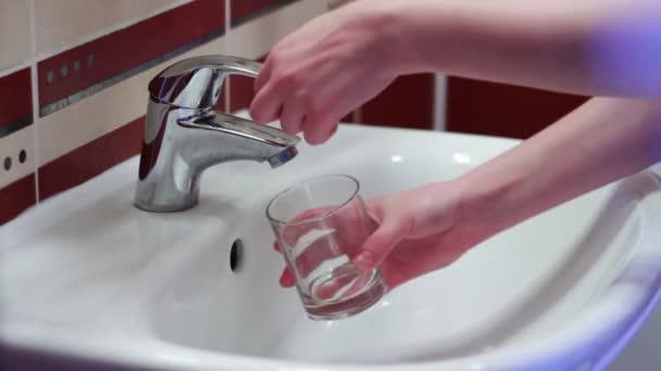 Muž sbírá vodu ve sklenici vody z vodovodu