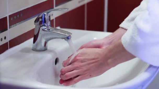 az ember mossa a kezét a mosogató