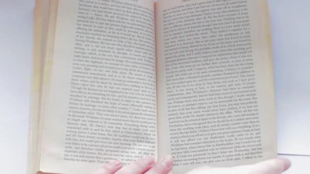 Rukou, obrací stránky knihy zprava doleva
