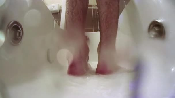 Man taking a shower, view of the legs.