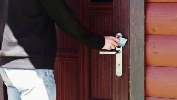 Az ember kinyitja az ajtót, hogy egy elektronikus kulcs - kártya.