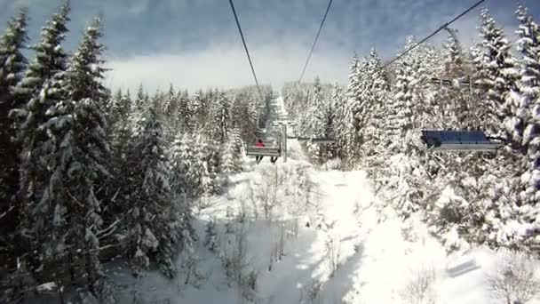 Lyžař se tyčí na lyžařské vleky. Panorama a krajiny, hory, zasněžené stromy. Pohled z lanovky