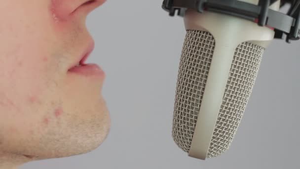 Man singing at studio microphone.