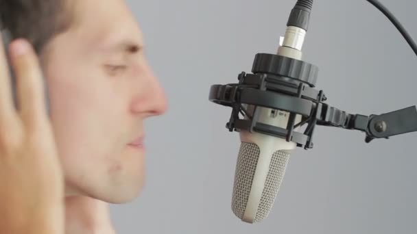 Man in headphones singing at studio microphone.