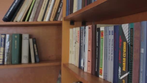 Dlouhý sál knihovny s dřevěnými regály na knihy