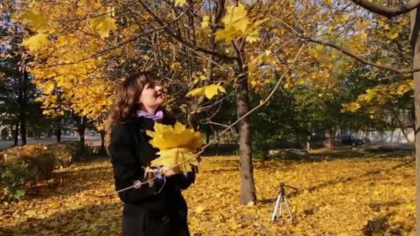 Ein Mädchen wirft im Herbstpark gelbe Blätter von den Ästen der Bäume.