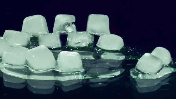 Eiswürfel schmilzt und bewegt sich auf einer Glasoberfläche