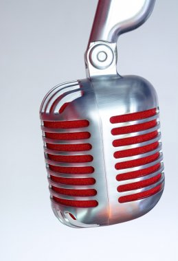 Silver vintage microphone with red membrane on a grey background