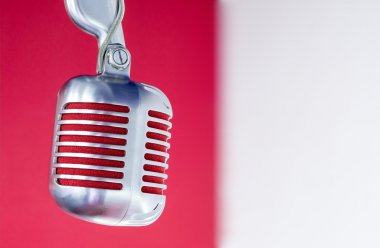 Silver vintage microphone with red membrane on a red-white background