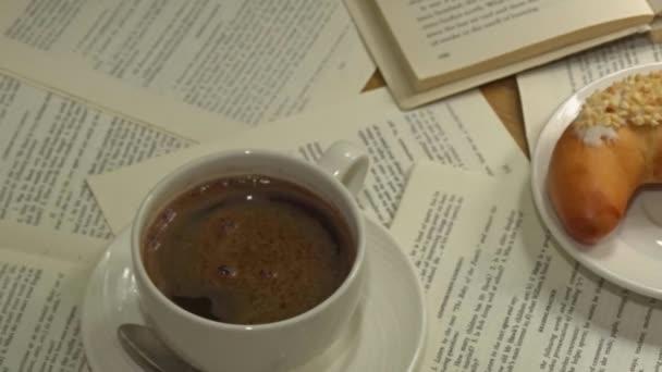 Bílý šálek kávy opravdu horké kouření na listech papírů knihu s dezert a otevřené knize na pozadí