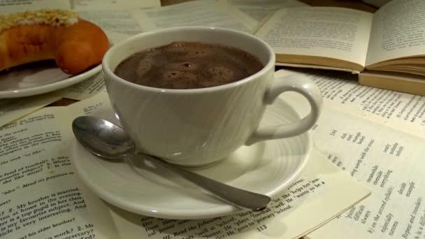 eine weiße Tasse wirklich heißen Raucherkaffee auf Buchpapier mit Dessert und aufgeschlagenem Buch auf Hintergrund