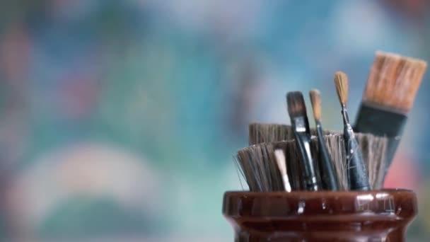 Použitý sortiment štětců sedících ve sklenici s rozmazaným barevným pozadím.