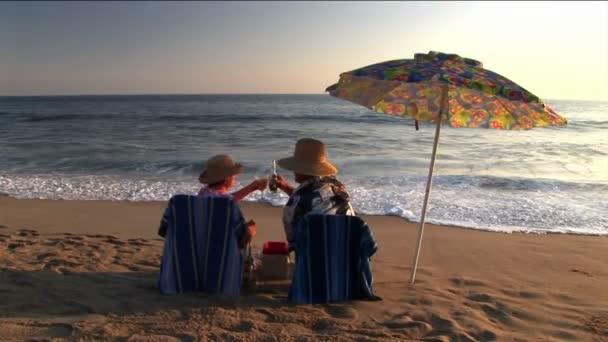 Un couple sous un parasol sur la plage de porter un toast et