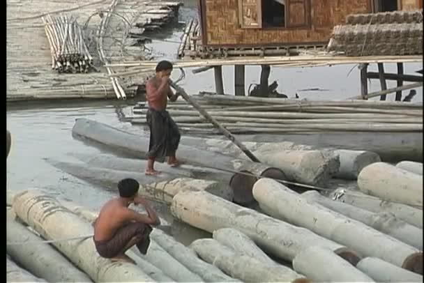Asian men walk along a log