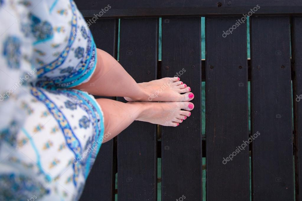 Bare feet girls on wooden bridge view from above