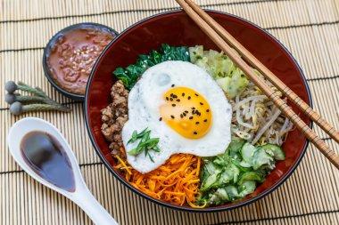 bibimbap in a bowl on bamboo mat, korean dish