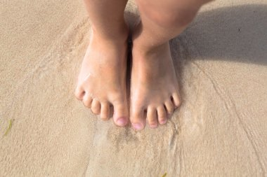 Bare feet little kid stand in the sand on beach, top view