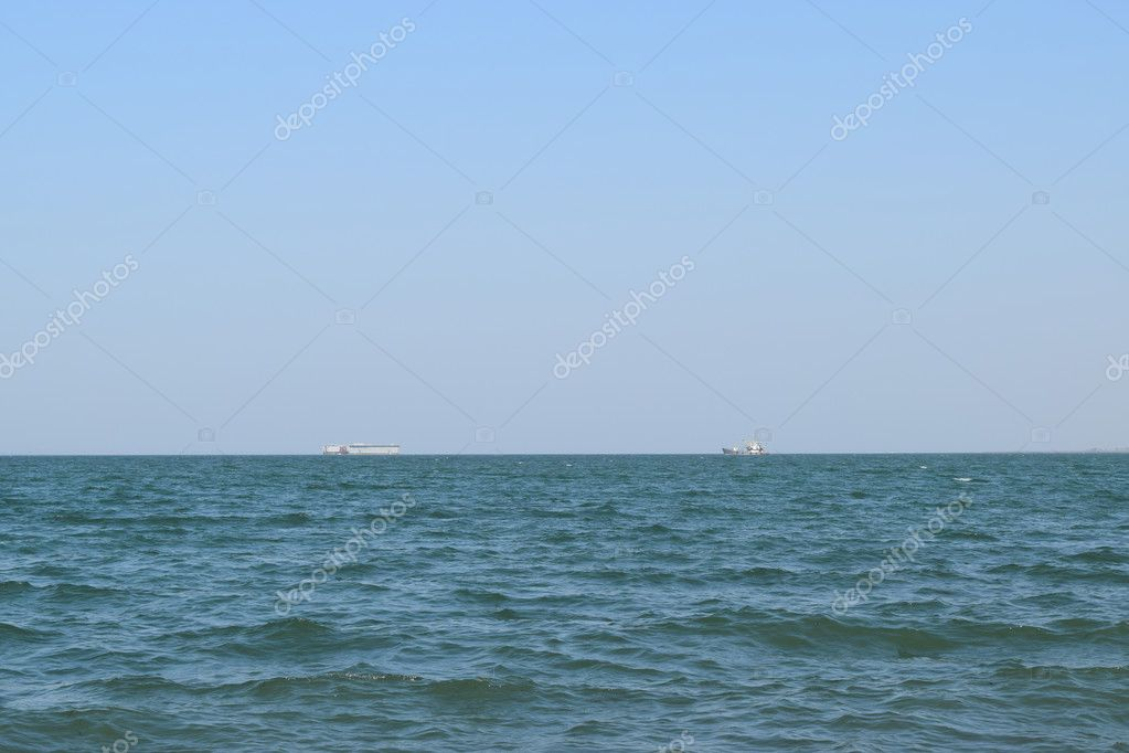 Seascape and two ships on the horizon. Sea day and small waves.