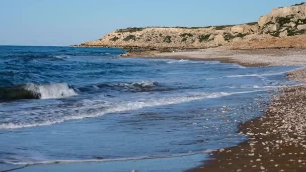 széles homokos strand és hullámzó tenger hullámok fehér vastag habos címerek alatt kék Ciprus partján ég