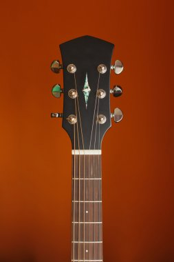 six-string acoustic guitar on a red background