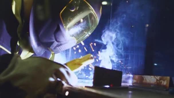 Tovární dělník svařuje kov. Ten chlap sváří. Svařování s argonem nebo elektrodou, pomocí svařovacího stroje. Průmyslový podnik vyrábějící kovové konstrukce. Jiskry a záblesky létají. Zpomalený pohyb.