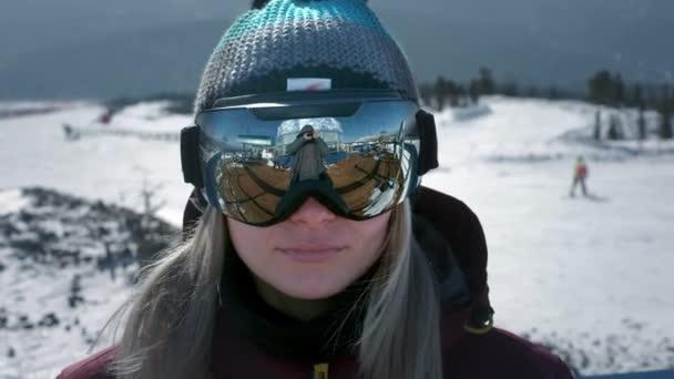 Ein schönes Mädchen setzt sich eine Winterbrille oder eine Maske zum Snowboarden auf. Das Konzept des Sieges im Sport, des Sieges, des Sieges. Vorbereitung auf das Skifahren auf einem verschneiten Hang. Winterreisen im Skigebiet