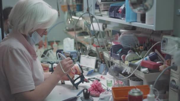 Eine erwachsene Medizinerin stellt im Labor eine Prothese her. Chirurg mit einer Zahnprothese. Fortschrittliche Technologie in der Zahnmedizin. Herstellung von Zahnimplantaten und künstlichen Zähnen. ROTES EPIC.