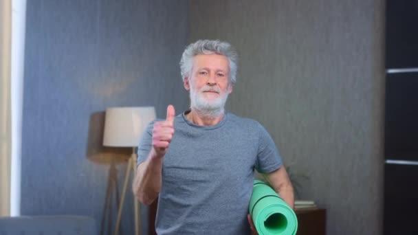 Der grauhaarige Senior lächelt, zeigt Daumen hoch, hält eine Yogamatte in der Hand. Dehnübungen zu Hause. Großvater in ausgezeichneter athletischer Körperform. Alter Mann in Sportkleidung. Gesundheit im Alter.