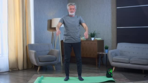 Portrait of a gray-haired senior man with a beard squats. Does home exercises. Grandfather in excellent athletic body shape. Old man in sportswear. Squatting for back health in old age