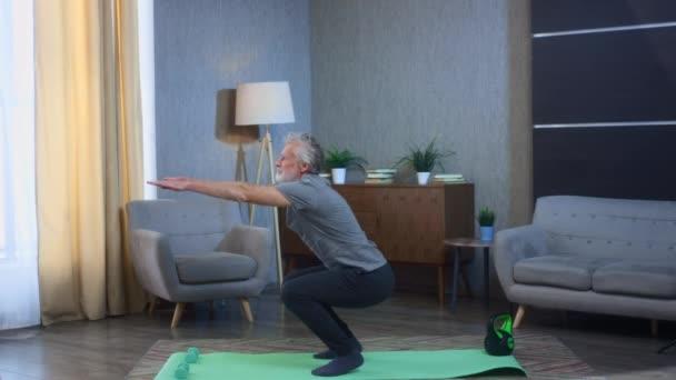 Porträt eines grauhaarigen älteren Mannes, der auf einer Yogamatte hockt. Heimfitness-Training hockt auf seinen Füßen. Großvater in ausgezeichneter athletischer Körperform. Alter Mann in Sportkleidung. Gesundheit im Alter
