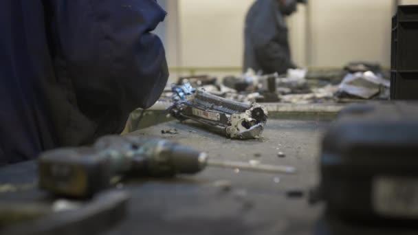 Mužský dělník třídí a recykluje elektronický odpad a šrot.
