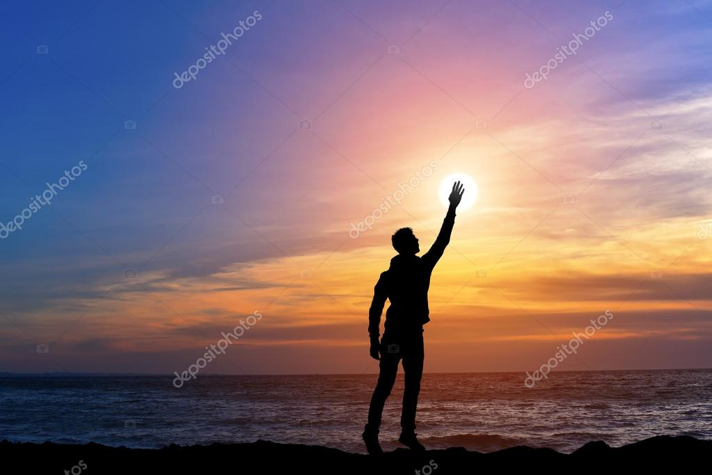 happy man with hand up on sunset background, man on top of the mountain reaches for the sun, silhouette man holding sun on the hill